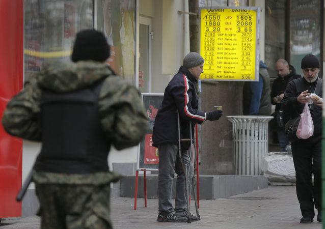 一個乞丐在基輔的外匯兌換點旁討要施捨