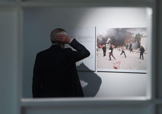 Посетитель выставки победителей и призеров Международного конкурса фотожурналистики имени Андрея Стенина в Москве