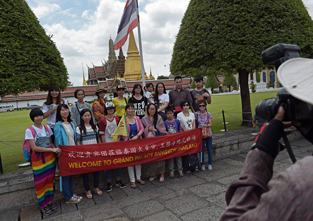 Chinese tourists pose for a group picture before visiting the Grand Palace in Bangkok
