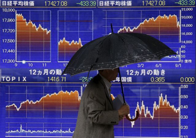 一名男性在日本证券指数走向的电子显示屏前走过。