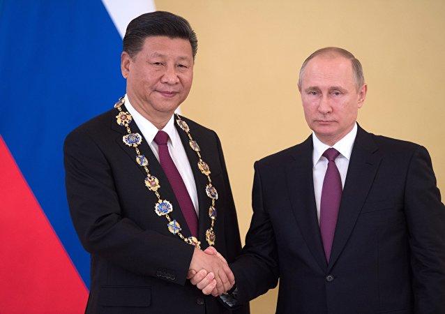 Президент РФ Владимир Путин и председатель Китайской Народной Республики (КНР) Си Цзиньпин, награжденный орденом Святого апостола Андрея Первозванного (слева) во время встречи