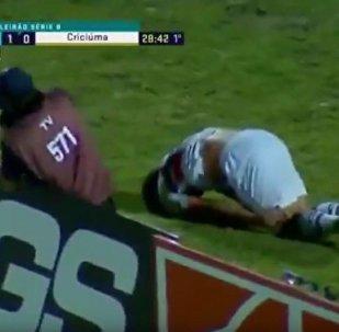 一名足球员在庆祝进球时撞到广告牌后翻了一个跟头并倒在地上