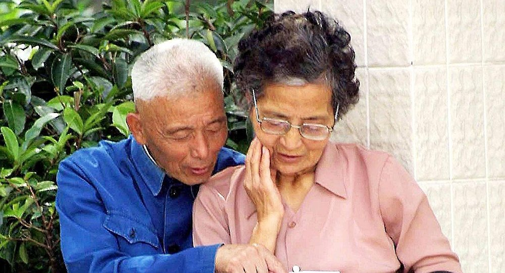 An elderly Chinese couple reads a tourist brochure