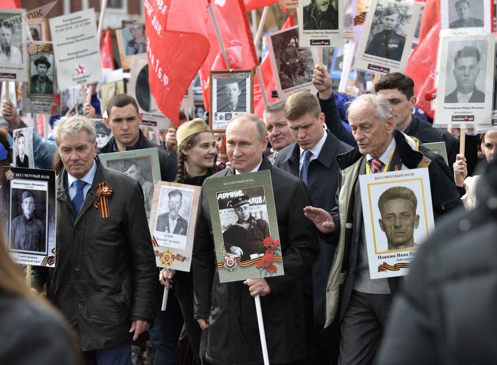 俄罗斯总统普京手捧父亲的肖像参加不朽的军团大游行。