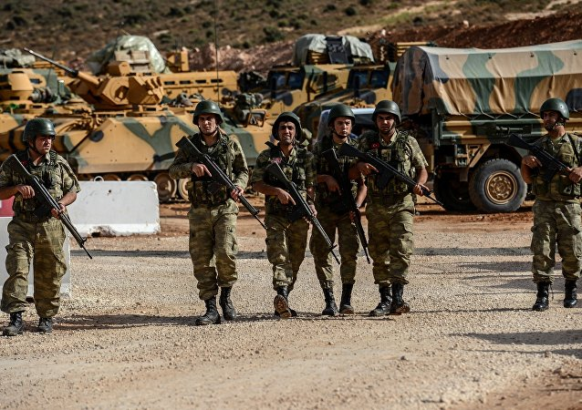 Turkish soldiers stand near armoured vehicles during a demonstration in support of the Turkish army's Idlib operation near the Turkey-Syria border