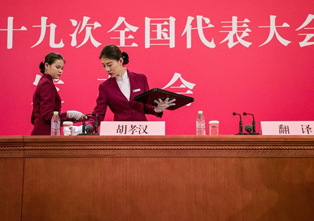 Hostesses set up a desk for a press conference prior to the opening session of the 19th Communist Party Congress