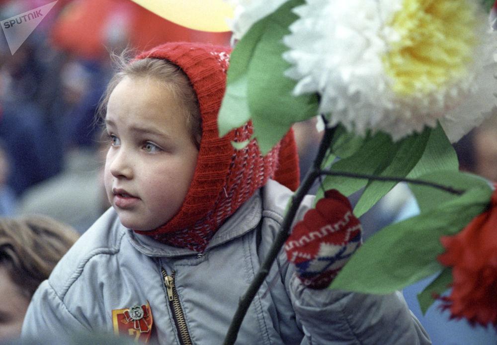 在紅場上的勞動者遊行隊伍中手拿鮮花的女孩