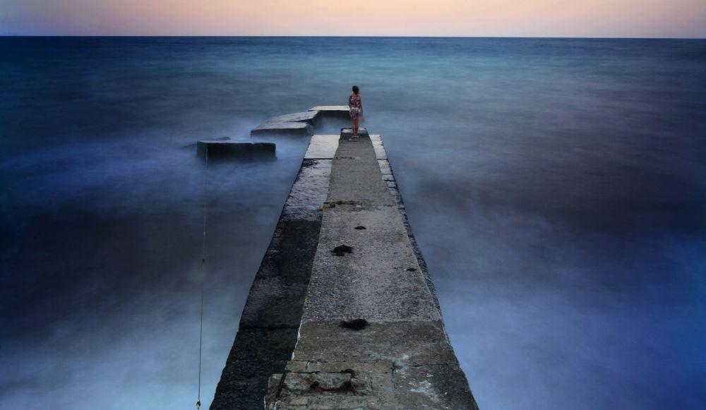 一女孩站在阿盧什塔的防波堤上