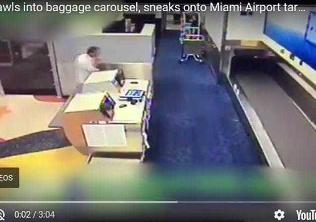 美國邁阿密機場一名乘客通過行李傳送帶進入機場跑道