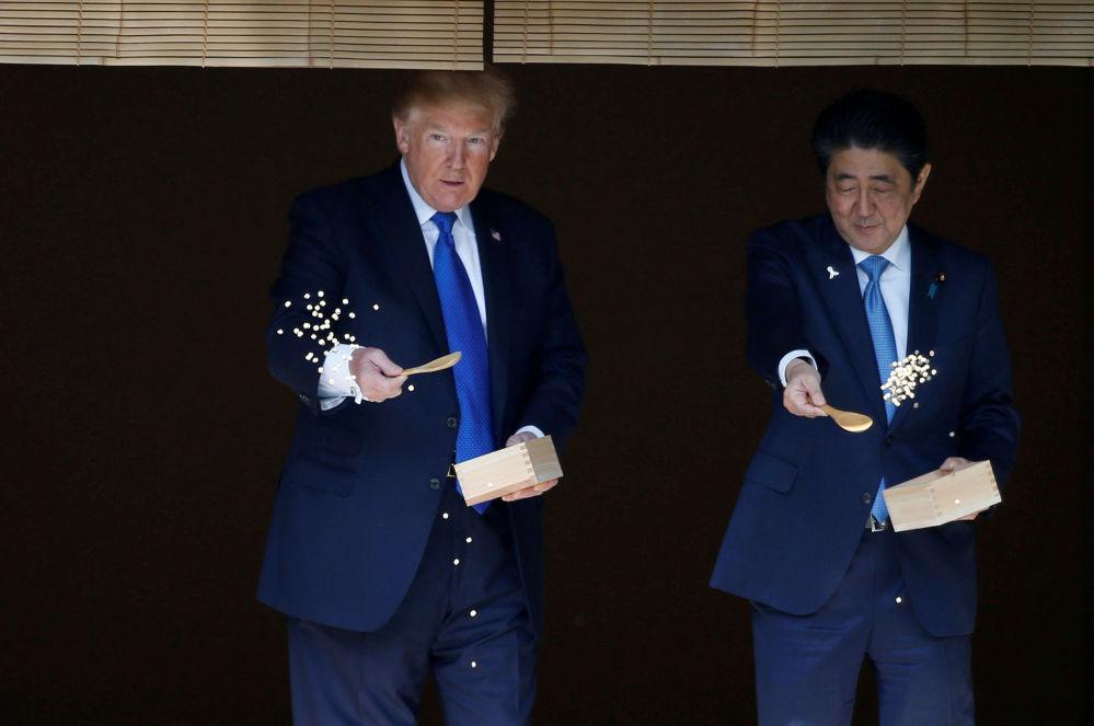 美国总统唐纳德·特朗普和日本首相安倍晋三在东京共进午餐前给锦鲤喂食
