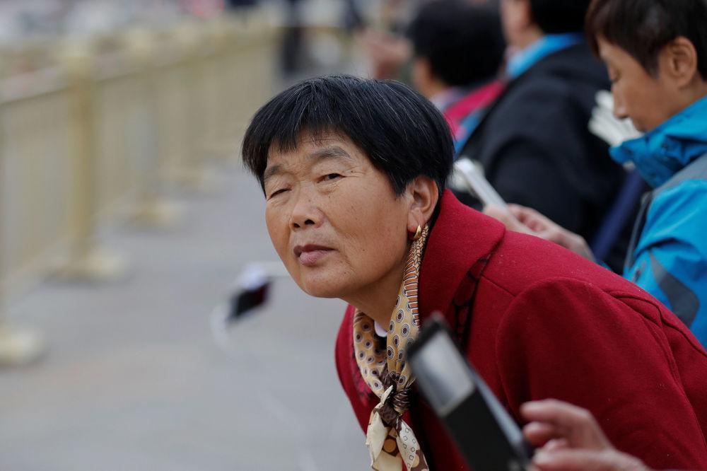 在美国总统唐纳德·特朗普的车队驶过北京天安门广场时,游客们企图看一眼美国总统