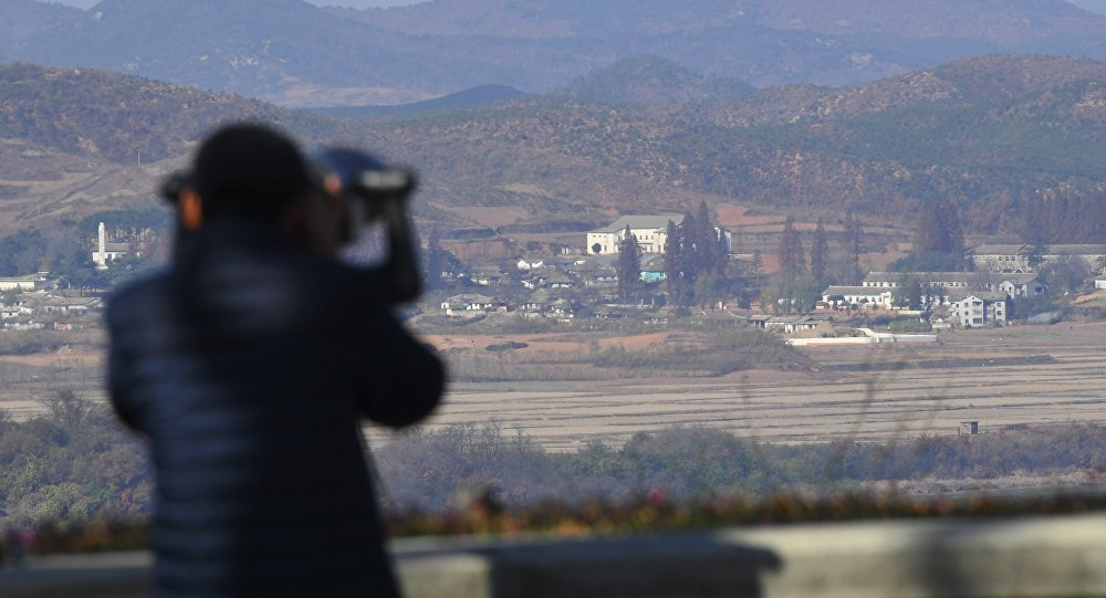 A woman looks through binoculars towards North Korea from a South Korean observation post in Paju near the Demilitarized Zone