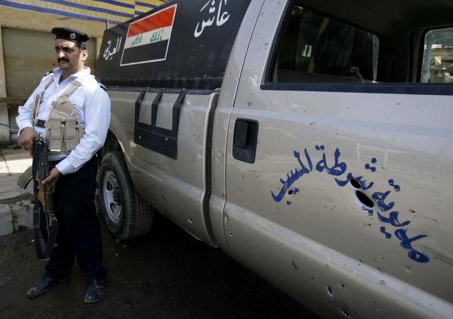 Иракский полицейский возле поврежденного полицейского автомобиля