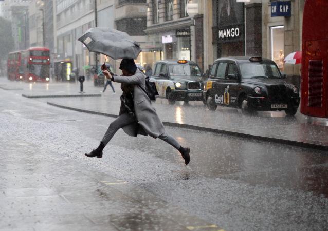 伦敦女孩雨中跳水坑(资料图片)