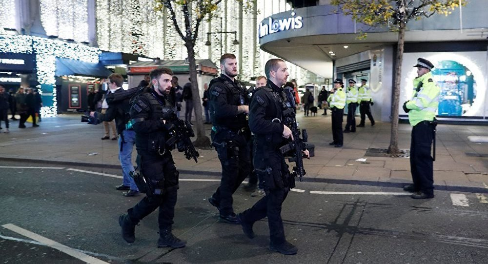 Armed police officers walk along Oxford Street, London
