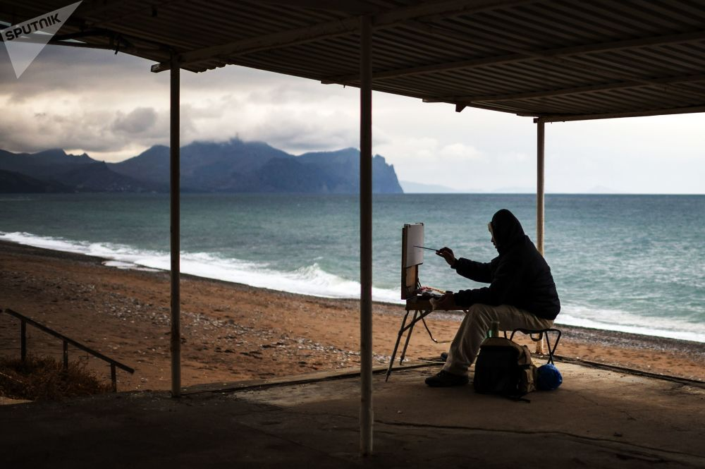 克里米亚塞瓦斯托波尔的一位画家正在一处沙滩上画画