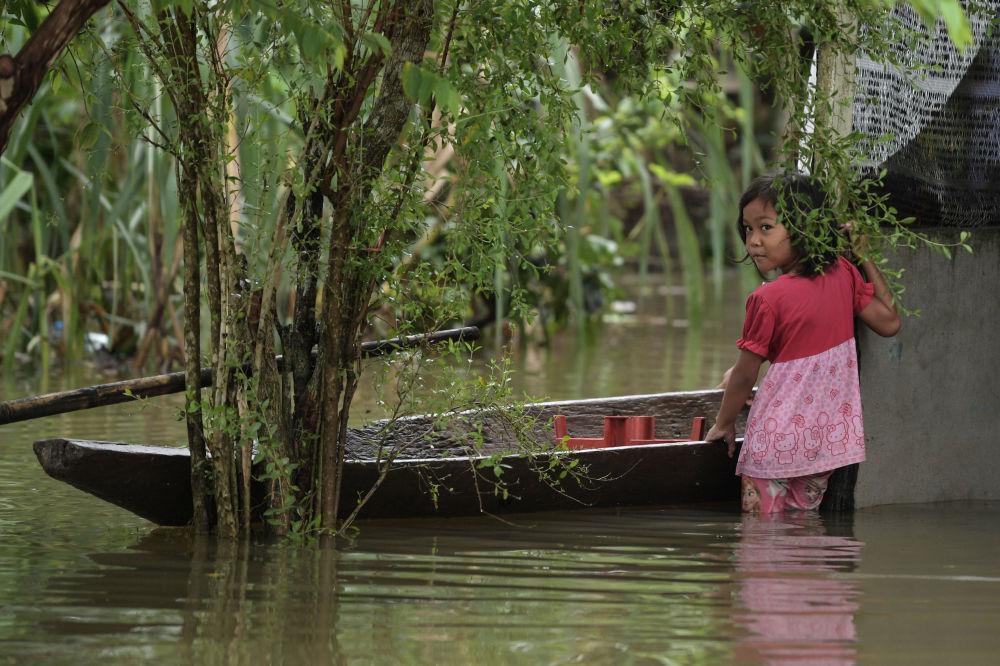 馬來西亞遇洪水襲擊,圖為一名小女孩站在一艘小船旁