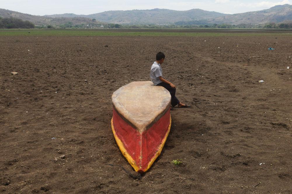 危地馬拉阿特斯卡滕帕湖邊,一個男孩坐在倒扣的船上凝視著乾涸的水域。