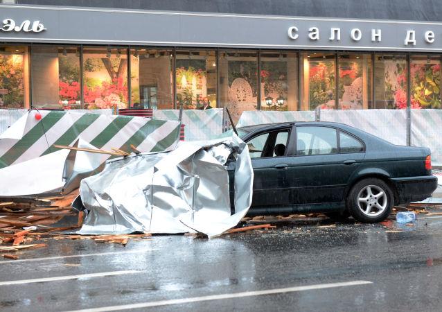 Сорванный ураганом рекламный щит на припаркованном автомобиле в Москве
