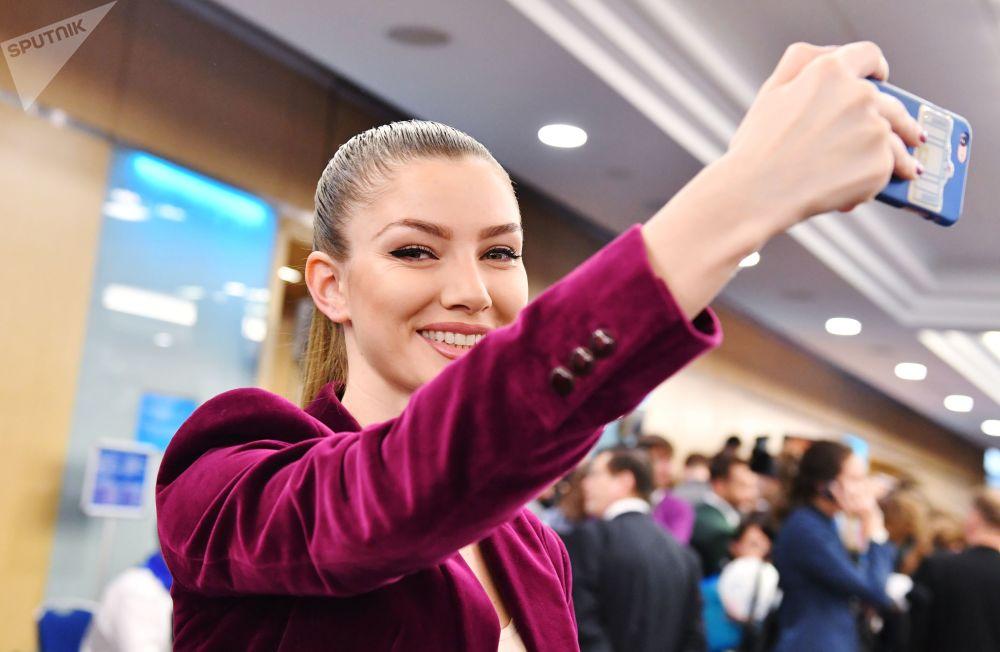 一名女記者在普京大型記者會開始前拍照。