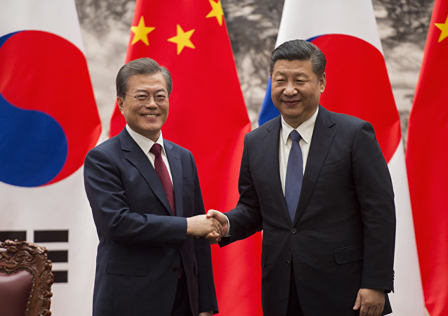 South Korean President Moon Jae-In (L) and Chinese President Xi Jinping (R) shake hands at the end of a signing ceremony at the Great Hall of the People in Beijing