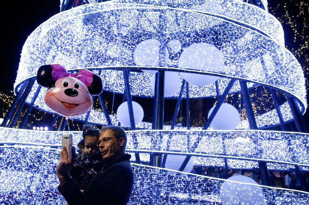 雅典一名男子帶著孩子在聖誕彩燈前自拍