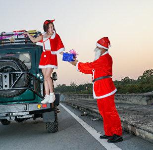 越南姑娘装扮成圣诞老人在俄产越野车旁照片