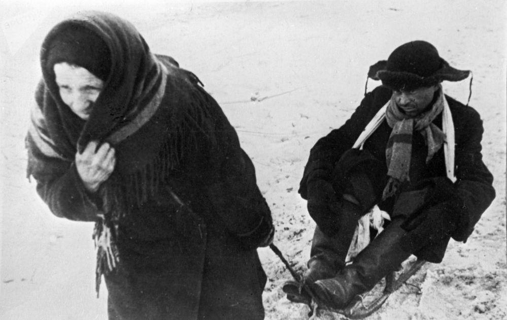 女子用雪橇拉著飢餓的丈夫