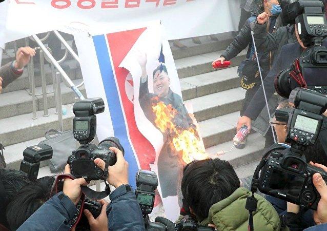 韩国抗议人烧毁朝鲜国旗和金正恩照片