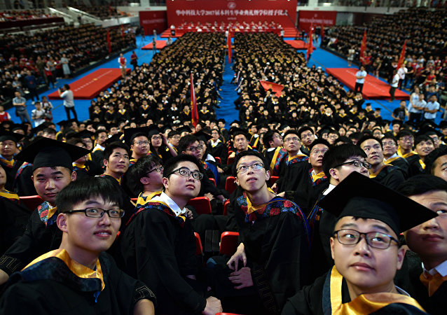 Students from the Huazhong University of Science and Technology taking part in their graduation ceremony in a sports stadium in Wuhan