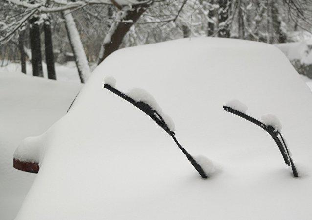 Машина, занесенная снегом, стоит во дворе во время снегопада в Москве