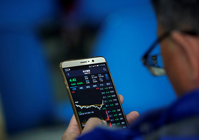 An investor checks stock information on a mobile phone at a brokerage house in Shanghai
