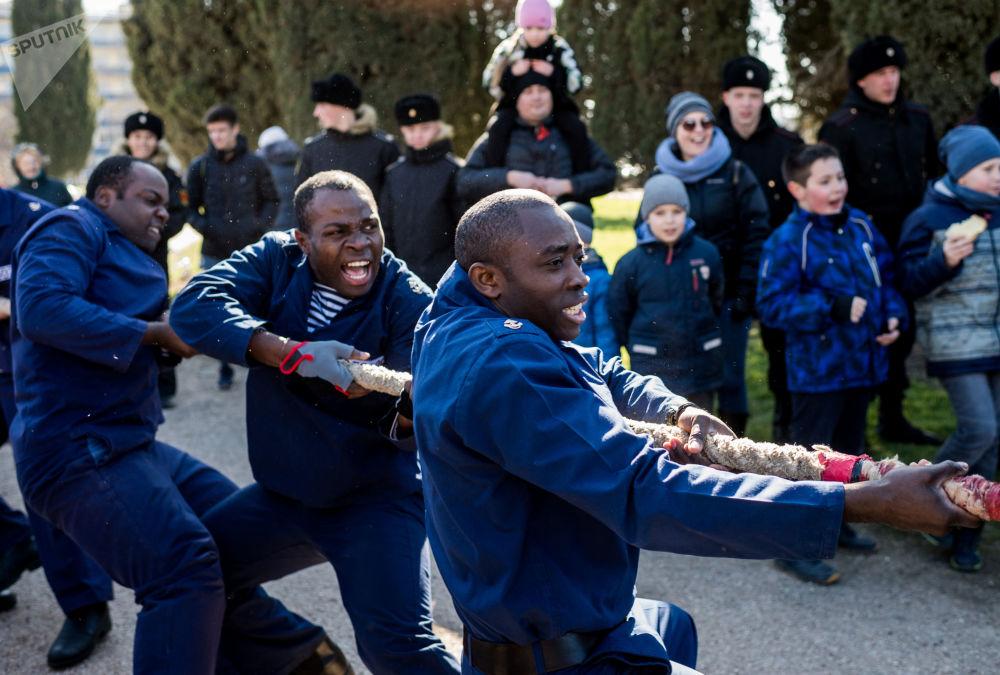 黑海纳西莫夫红星勋章高等海军学校的学员们在塞瓦斯托波尔举行的谢肉节庆祝活动上参加拔河比赛