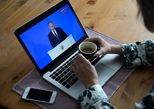 Девушка у себя в квартире в Новосибирске смотрит трансляцию ежегодного послания президента РФ Владимира Путина к Федеральному собранию