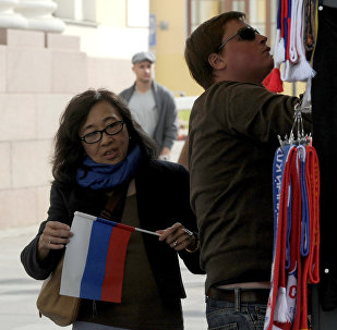 Chinese tourist holds Russian flag near a gift kiosk in central St. Petersburg
