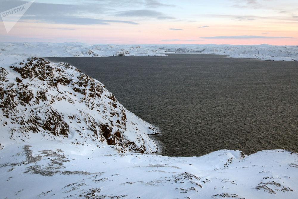 笼罩在摩尔曼斯克州科拉半岛捷里别尔斯卡娅湾石质海岸的冬日阳光