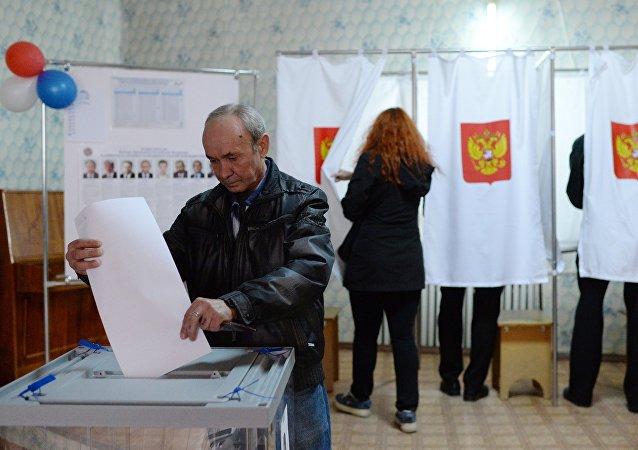 Мужчина опускает бюллетень во время голосования на выборах президента Российской Федерации на избирательном участке в Крыму