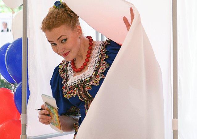 Девушка в национальном костюме выходит из кабинки во время голосования на выборах президента Российской Федерации в Сочи