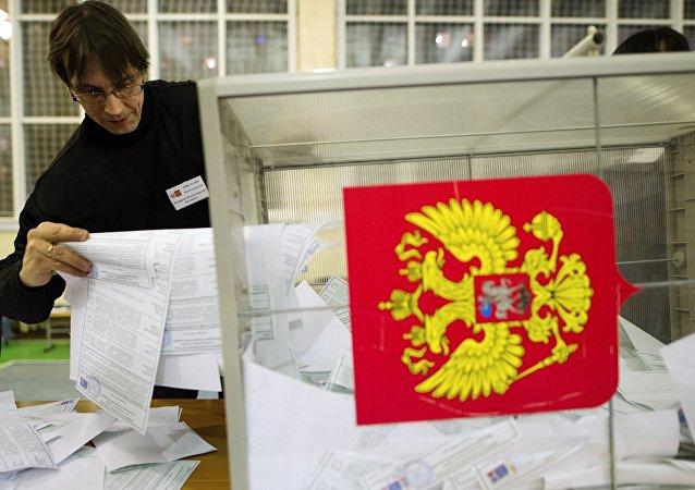 Члены участковой избирательной комиссии высыпают бюллетени для подсчета голосов на одном из избирательных участков в Новосибирске
