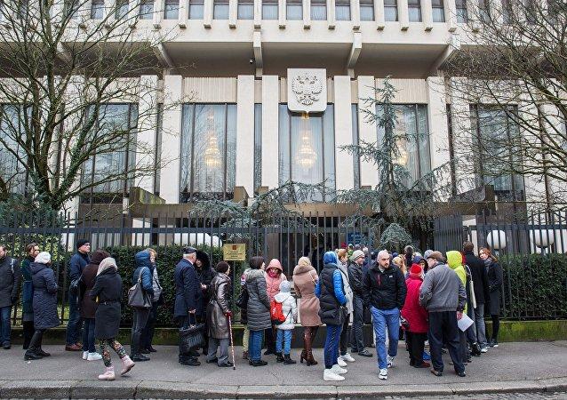 Избиратели у здания посольства России во Франции, где проходит голосование на выборах президента России