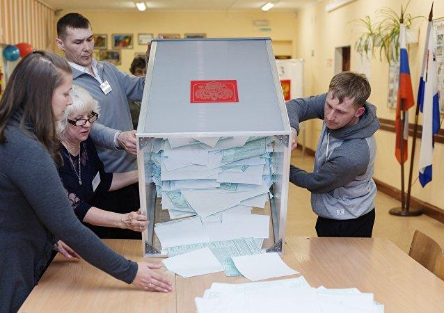 Члены участковой избирательной комиссии вскрывают избирательную урну перед подсчетом голосов на выборах президента РФ