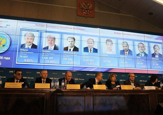Портреты кандидатов в президенты РФ с данными по голосованию за них на экране в информационном центре Центральной избирательной комиссии РФ