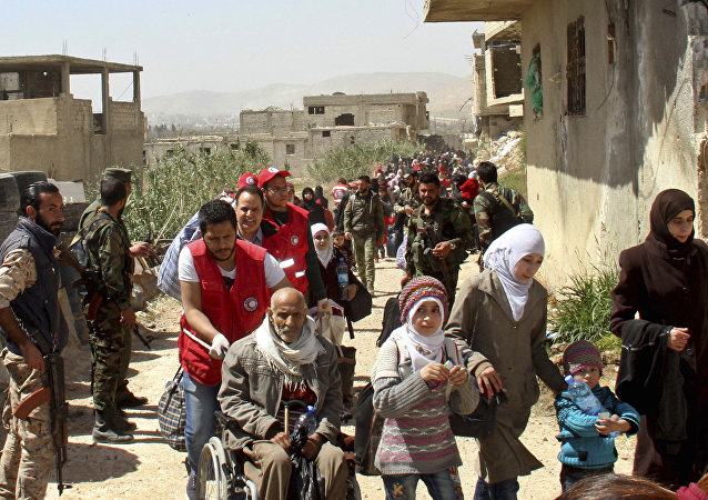 Civilians carrying their belongings leaving towns and villages, in the eastern Ghouta region near Damascus