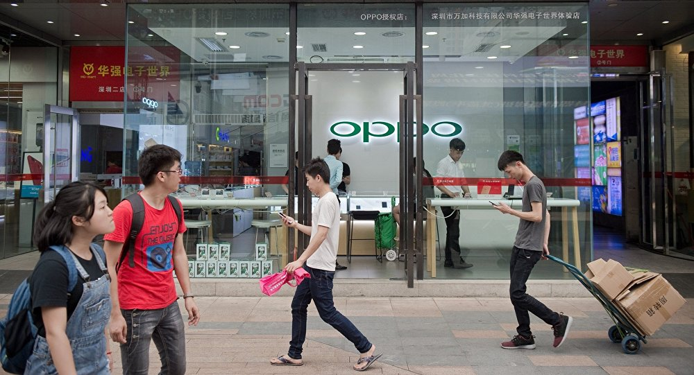 People walk in front of an Oppo shop in Shenzhen
