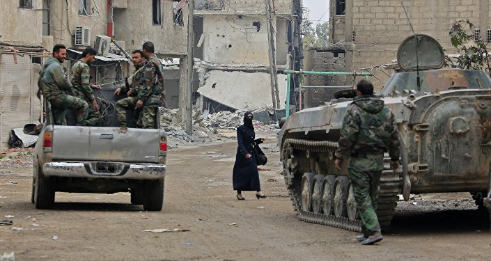 Syrian government forces' infantry fighting vehicles (IFVs) and trucks drive past damaged buildings down a street in the Eastern Ghouta town of Hazzeh