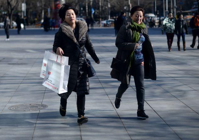 Женщины с пакетами после шопинга на улице Пекина, Китай