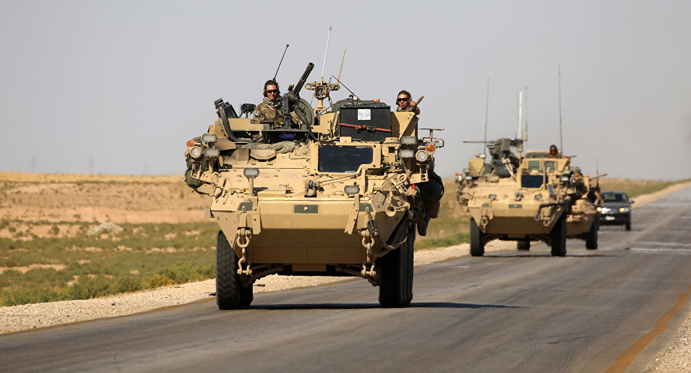 US troops sit atop an armoured vehicle on a road near the northern Syrian village of Ain Issa