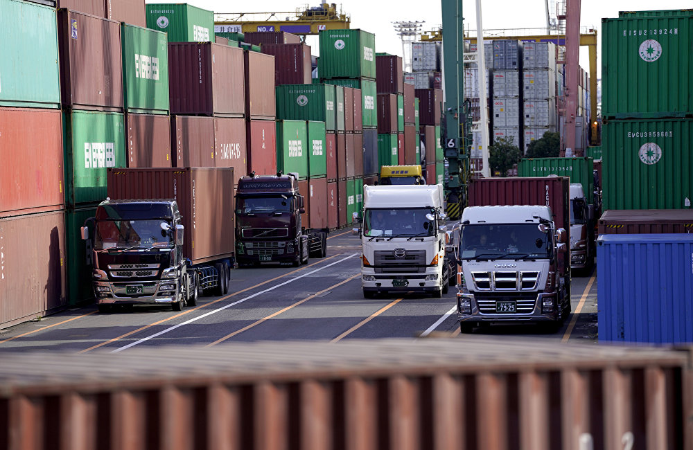 Container trucks leave a cargo terminal at a port in Tokyo