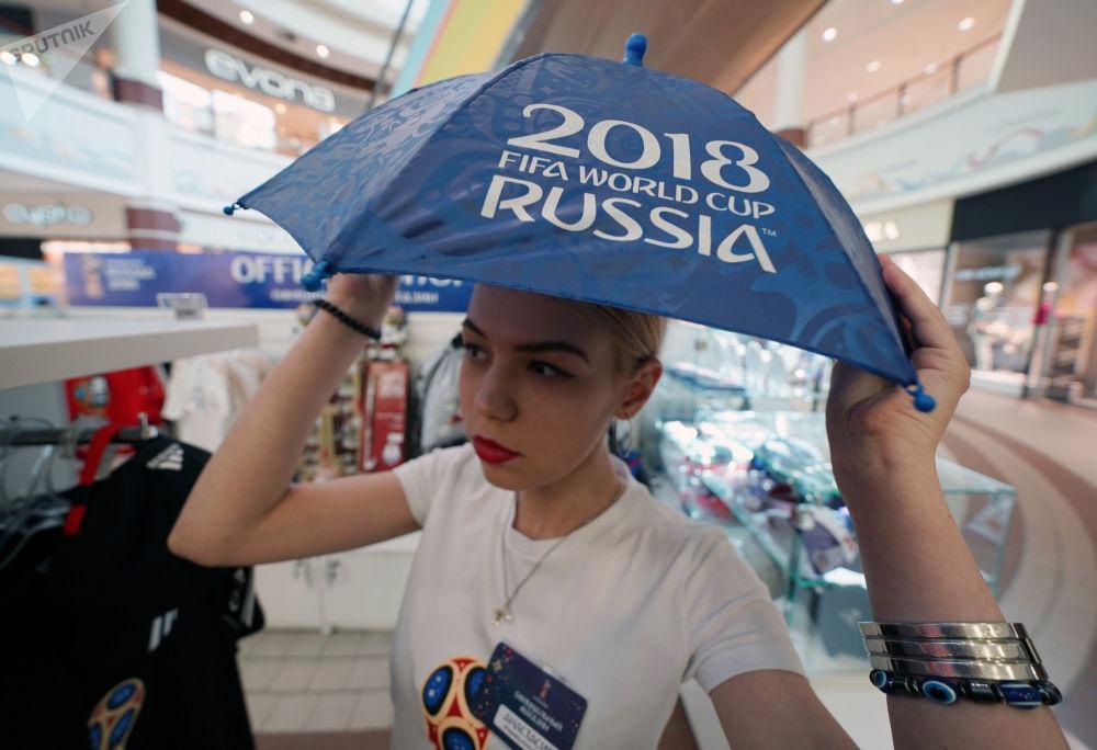 一名拿伞的女孩正在逛世界杯官方纪念品和服饰商店。