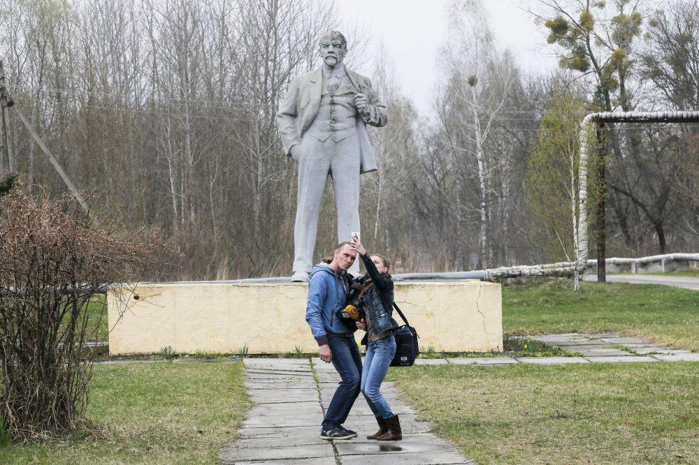 记者在乌克兰切尔诺贝利的列宁纪念碑前自拍